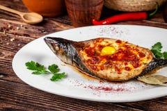 Concepto de cocina georgiana Caballa cocida Adzhar de los pescados Platos de porción en el restaurante georgiano en la placa blan imagenes de archivo