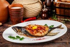 Concepto de cocina georgiana Caballa cocida Adzhar de los pescados Platos de porción en el restaurante georgiano en la placa blan imagen de archivo