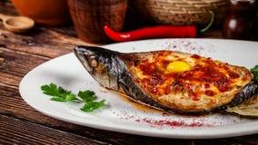 Concepto de cocina georgiana Caballa cocida Adzhar de los pescados Platos de porción en el restaurante georgiano en la placa blan imagen de archivo libre de regalías