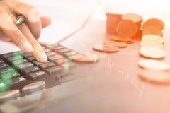 Concepto de comercio de divisas La pila de monedas y de una tenencia de la mano está examinando una carta técnica del instrumento foto de archivo libre de regalías