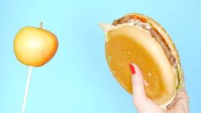 Concepto de comida sana y malsana Yaloko contra las hamburguesas en un fondo azul brillante Manos femeninas con el clavo rojo almacen de metraje de vídeo