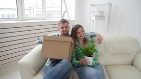 Concepto de compra y de alquilar las propiedades inmobiliarias Los pares jovenes de la familia compraron o alquilaron su primer p almacen de metraje de vídeo