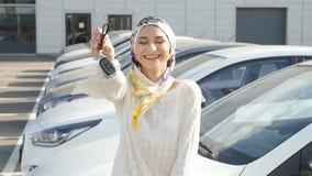 Concepto de comprar un coche Mujer musulmán feliz que lleva a cabo llave del coche almacen de metraje de vídeo