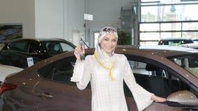 Concepto de comprar un coche Mujer musulmán feliz que lleva a cabo llave del coche metrajes