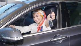Concepto de comprar un coche Mujer musulmán feliz que lleva a cabo llave del coche almacen de video
