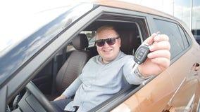 Concepto de comprar y de alquilar un coche Hombre feliz con llaves del coche cerca de la sala de exposición almacen de video