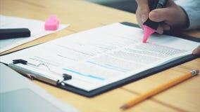 Concepto de contabilidad: los marcadores de la mano son un número importante en un documento Verificación de documentos important almacen de metraje de vídeo
