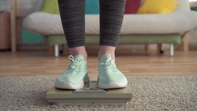 Concepto de control de peso, los pies de las mujeres en las escalas del piso metrajes
