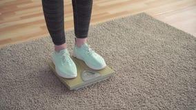 Concepto de control de peso, los pies de las mujeres en las escalas del piso en la sala de estar almacen de video
