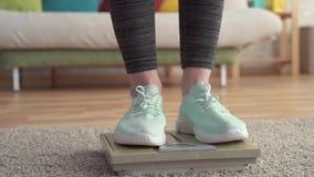 Concepto de control de peso, los pies de las mujeres en las escalas MES lento del piso almacen de video