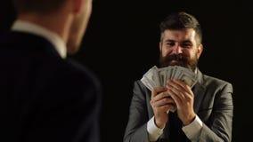 Concepto de corrupción Un hombre en un traje se jacta el dinero delante de otro hombre almacen de metraje de vídeo