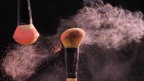 Concepto de cosméticos y de belleza Cepillos del maquillaje con la explosión rosada del polvo en fondo negro almacen de video