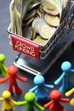 Concepto de Crowdfunding con la estatuilla y la carretilla multicoloras de las compras por completo del dinero en fondo oscuro fotos de archivo libres de regalías