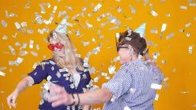 Concepto de d?a de fiesta y de cumplea?os Baile feliz joven de los pares en sombreros en fondo anaranjado con confeti almacen de metraje de vídeo