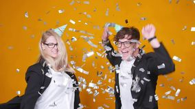 Concepto de d?a de fiesta y de cumplea?os Baile feliz joven de los pares en sombreros en fondo anaranjado con confeti almacen de video
