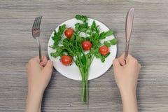 Concepto de dieta de la bajo-caloría El ` s de la mujer da sostener los cubiertos y el re foto de archivo libre de regalías