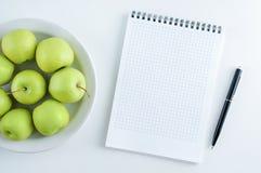 Concepto de dieta Manzanas verdes en una placa blanca y un cuaderno con una pluma imagen de archivo libre de regalías