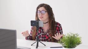 Concepto de difusiones que bloguean y video El vídeo o la difusión femenino joven de la grabación del blogger vive en smartphone almacen de video