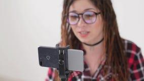 Concepto de difusiones que bloguean y video El v?deo o la difusi?n femenino joven de la grabaci?n del blogger vive en smartphone metrajes