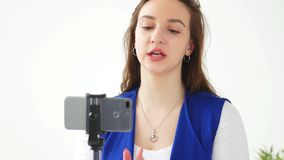 Concepto de difusiones que bloguean y video El v?deo o la difusi?n femenino joven de la grabaci?n del blogger vive en smartphone almacen de metraje de vídeo