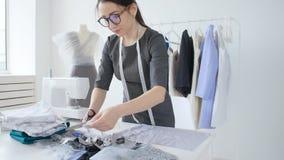Concepto de diseño y producción de ropa Diseñador de ropa joven de la costurera que trabaja en su estudio metrajes