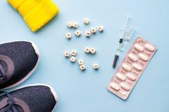 Concepto de doping en deporte Medicina de la inscripción o doping en un fondo azul Zapatos de los deportes, píldoras, jeringuilla imagenes de archivo