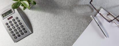 Concepto de educación, de trabajo con la calculadora, de pluma, de tablero y de lentes Imagen de archivo