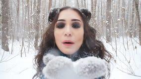 Concepto de entretenimiento del invierno Mujer joven en parque del invierno con nieve en manos almacen de metraje de vídeo