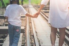 Concepto de familia adorable: Mujer y niños que caminan en pistas de ferrocarril y que llevan a cabo la mano así como la mirada a fotografía de archivo libre de regalías