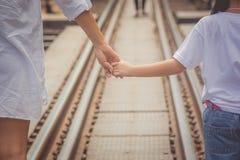 Concepto de familia adorable: Mujer y niños que caminan en pistas de ferrocarril y que llevan a cabo la mano así como la mirada a fotos de archivo libres de regalías