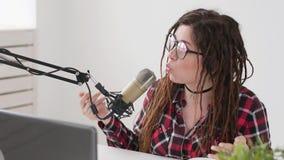 Concepto de fluir y de difusi?n La muchacha alegre joven en el estudio habla en un micr?fono almacen de video
