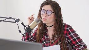 Concepto de fluir y de difusi?n La muchacha alegre joven en el estudio habla en un micr?fono almacen de metraje de vídeo
