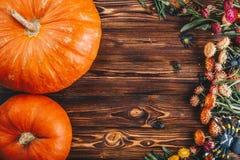 Concepto de Halloween con las calabazas y las flores frescas con las arañas en la tabla de madera Opinión del truco o de invitaci Foto de archivo