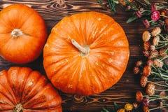 Concepto de Halloween con las calabazas y las flores frescas en la tabla de madera Opinión del truco o de invitación desde arriba Imagenes de archivo