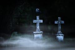 Concepto de Halloween, cruces de piedra en la noche en el cementerio de niebla Fotos de archivo libres de regalías