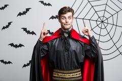Concepto de Halloween del vampiro - retrato del caucásico hermoso en el traje de Halloween del vampiro poining en lado Imagen de archivo