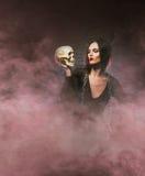 Concepto de Halloween: la bruja joven y atractiva hace la brujería Imagen de archivo