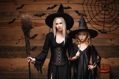 Concepto de Halloween - madre alegre y su hija en trajes de la bruja que celebran Halloween que presenta con las calabazas curvad Imagenes de archivo