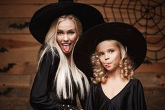 Concepto de Halloween - madre caucásica hermosa del primer y su hija en trajes de la bruja que celebran Halloween que presenta co Foto de archivo libre de regalías