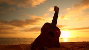 Concepto de Hawaii con el ukelele en la playa en la puesta del sol