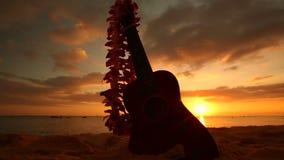 Concepto de Hawaii con el ukelele y leus en la playa en la puesta del sol
