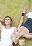 Concepto de Healthylife: Pares jovenes de los jugadores de tenis que descansan sobre T Imagen de archivo