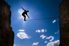 Concepto de hombre de la asunción de riesgos que equilibra en la cuerda Imagen de archivo libre de regalías