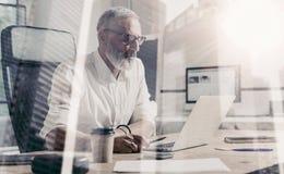 Concepto de hombre de negocios barbudo adulto que lleva vidrios clásicos y que trabaja en la tabla de madera con el ordenador por Imagenes de archivo