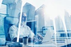 Concepto de hombre de negocios barbudo adulto que lleva vidrios clásicos y que trabaja en la tabla de madera con el ordenador por Imagen de archivo libre de regalías
