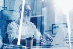 Concepto de hombre de negocios barbudo adulto que lleva vidrios clásicos y que trabaja en la tabla de madera con el ordenador por Imagen de archivo