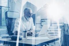 Concepto de hombre de negocios elegante adulto que lleva vidrios clásicos y que trabaja en la tabla de madera con el ordenador po Imagenes de archivo
