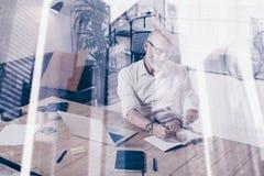 Concepto de hombre de negocios elegante adulto que lleva vidrios clásicos y que trabaja en la tabla de madera en lugar coworking  Foto de archivo libre de regalías