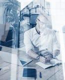 Concepto de hombre de negocios elegante adulto que lleva vidrios clásicos y que trabaja en la tabla de madera en lugar coworking  Fotos de archivo libres de regalías