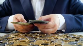 Concepto de hombre de negocios codicioso Hombre joven en el traje que se sienta en el escritorio por completo del dinero y que cu almacen de metraje de vídeo